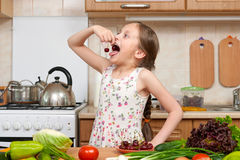 Child girl eat cherries, fruits and vegetables in home kitchen i Stock Image