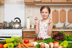 Child girl eat cherries, fruits and vegetables in home kitchen interior, healthy food concept Royalty Free Stock Photos
