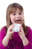 Child girl eating chocolate. Portrait of child girl eating chocolate isolated on white background Royalty Free Stock Photos