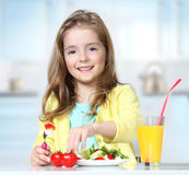 Child girl eating fresh salad vegetables at table indoors. Royalty Free Stock Photography