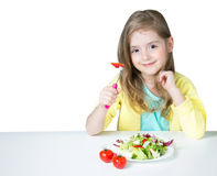 Child girl eating salad at table isolated on white. Stock Photo
