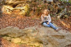 Child girl eating a sandwich in a forest surrounded by autumn le stock photo