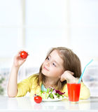 Child girl eating tomatoes fresh salad empty space background. Royalty Free Stock Photo