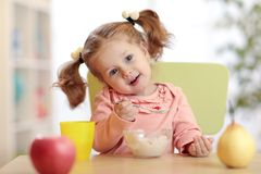 Child girl eating yoghurt with fruits at home or daycare centre Royalty Free Stock Photography