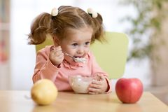 Child eating yogurt. Child girl eating yogurt or fresh cheese with fruits Royalty Free Stock Photo