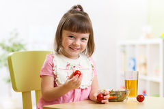 Child girl eats dinner and shows tomatoes Royalty Free Stock Photography