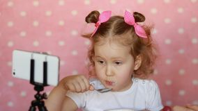 Child girl eats food and looks cartoons on the smartphone. Baby and gadgets, applications, internet, games