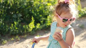 Child girl eats ice cream in sunglasses on a sunny summer day. stock video footage
