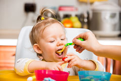 Child girl eats porridge from a spoon on kitchen. Stock Image
