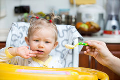 Child girl eats porridge from a spoon on kitchen. Stock Photography