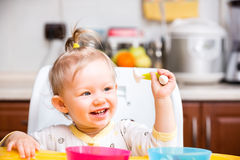 Child girl eats porridge from a spoon on kitchen. Stock Photos