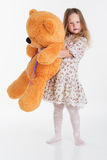 Child girl embraces big teddy bear Stock Photography