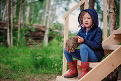 Child girl with empty bird nest on wooden stairs in summer forest Royalty Free Stock Images