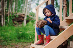 Child girl with empty bird nest on wooden stairs in summer forest Royalty Free Stock Photo