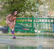 Child girl enjoying her leisure time by playing in outdoor kids water park Stock Photos