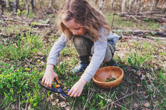 Child girl exploring nature in early spring forest. Kids learning to love nature. Teaching children about seasons changing.