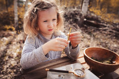 Child girl exploring nature in early spring, looking at first sprouts with loupe. Stock Image