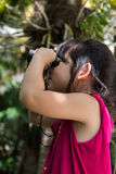 Child, Girl, Exploring via Binoculars. Cute girl is looking through binoculars during a trip Stock Image
