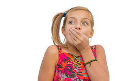 Child girl expressing shock emotion. Shocked child girl cover her mouth with hand in surprised expression Stock Photo