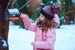 Child girl feeding birds in winter. Bird feeder in snowy garden, helping birds during cold season stock image