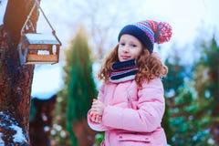 Child girl feeding birds in winter. Bird feeder in snowy garden, helping birds during cold season royalty free stock photo