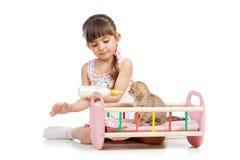 Child girl feeding and playing kitten cat Stock Photo