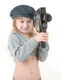 Child girl - filmmaker. Friendly girl - filmmaker  in walking clothing with old camera Royalty Free Stock Photo