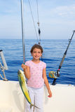 Child girl fishing in boat with mahi mahi dorado fish catch. With rod and trolling reels Royalty Free Stock Photography