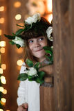 Child girl in  flower wreath on wooden background. Child girl in a flower wreath on brown wooden background and lights Stock Photos