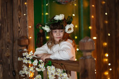 Child girl in  flower wreath on wooden background. Child girl in a flower wreath on brown wooden background and lights Stock Photography