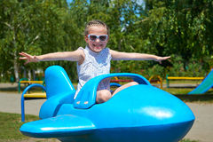 Child girl fly on blue plane attraction in city park, happy childhood, summer vacation concept Royalty Free Stock Image