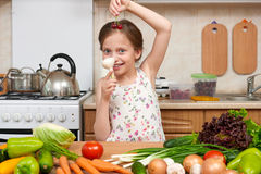 Child girl with fruits and vegetables in home kitchen interior, Royalty Free Stock Image