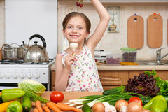 Child girl with fruits and vegetables in home kitchen interior, healthy food concept, hold garlic in hands Stock Photos