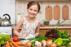 Child girl with fruits and vegetables in home kitchen interior, read cooking book, healthy food concept Royalty Free Stock Photo