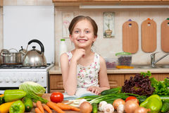 Child girl with fruits and vegetables in home kitchen interior, read cooking book, healthy food concept Stock Photography
