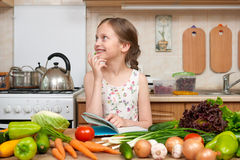 Child girl with fruits and vegetables in home kitchen interior, read cooking book, healthy food concept Royalty Free Stock Images