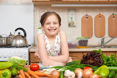 Child girl with fruits and vegetables in home kitchen interior, read cooking book, healthy food concept Royalty Free Stock Photos