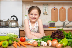 Child girl with fruits and vegetables in home kitchen interior, read cooking book, healthy food concept Stock Images