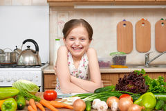 Child girl with fruits and vegetables in home kitchen interior, Stock Photo