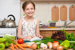 Child girl with fruits and vegetables in home kitchen interior, Royalty Free Stock Photo