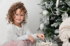 Child girl with gifts near Christmas tree Stock Images