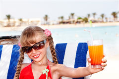 Child girl in glasses and red bikini drink  juice. Child girl in sunglasses and red bikini drink orange juice Stock Images