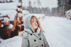 Child girl in grey coat on the walk in snowy forest with tree felling Royalty Free Stock Image