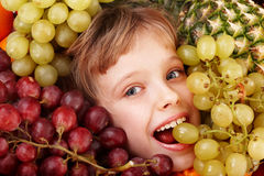 Child girl in group of fruit. Healthcare. Royalty Free Stock Photography