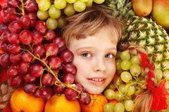 Child girl in group of fruit. Stock Photos