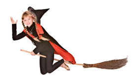 Child girl Halloween witch in black fly on broom. Royalty Free Stock Images