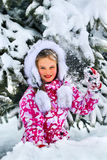 The child, a girl, happily playing in the snow. Stock Photo