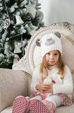 Child girl in hat with sheep toy and Christmas tree Royalty Free Stock Photography