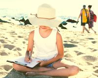 Child girl in hat writes draws dreams with sand on seashore. In summer Royalty Free Stock Photography