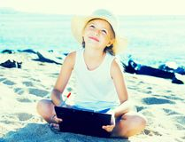 Child girl in hat writes draws dreams with sand on seashore. In summer Royalty Free Stock Photo